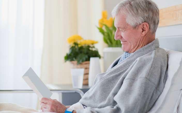 Paciente sonriente leyendo una nota de recuperación en un hospital