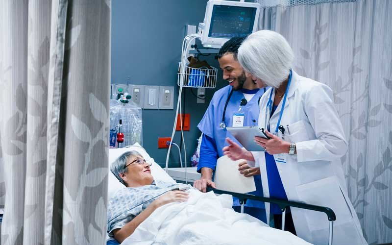 Doctor and nurse speaking with woman patient in ER hospital bed
